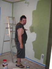 Mike Wilton paints his babies bedroom walls green.