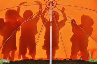 Silhouette of children playing behind an umbrella
